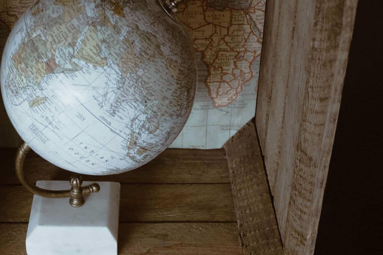 Kleiner Globus in einer Holzkiste mit Weltkarte