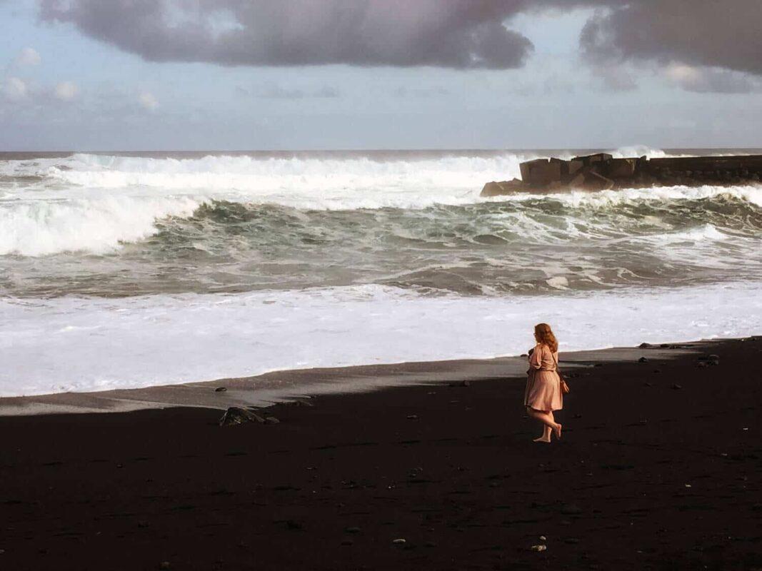 Spazieren auf dem schwarzen Sand